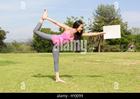 Beautiful woman doing yoga outdoors holding a blank piece of paper. - Stock Photo