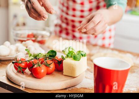 Woman preparing pizza in the kitchen - Stock Photo