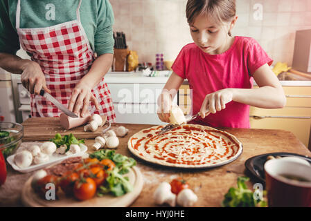 Mother and daughter preparing pizza in the kitchen - Stock Photo