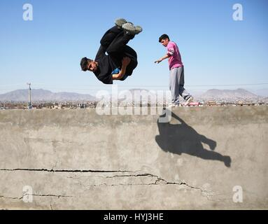 Kabul, Afghanistan. 4th April, 2017. An Afghan youth performs his Parkour skills from top of a wall in Kabul, capital - Stock Photo