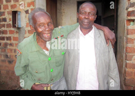 Mugomba, Uganda. 21st Feb, 2017. 91-year-old war veteran, Elismus Katende (L), wearing his old uniform while leaning - Stock Photo