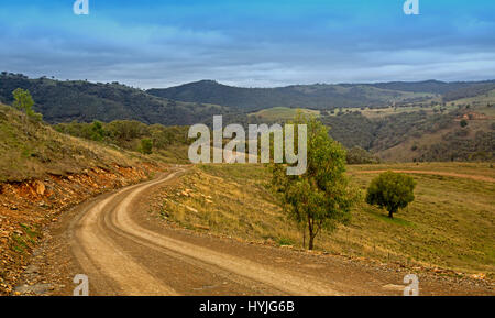 Narrow dirt road winding through vast  landscape of forested hills and valleys of Great Dividing Range under blue - Stock Photo