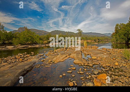 Panoramic view of rocky course of Mann River hemmed with forests & with ranges on horizon under blue sky near Coombadja - Stock Photo