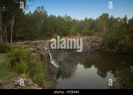 Waterfall cascading over high rocky cliff into calm waters of deep pool at Tooloom falls among forests in northern - Stock Photo