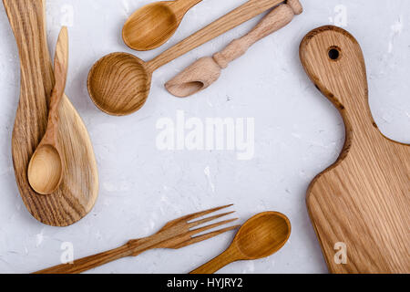 Frame of kitchen wooden utensils. Oak wood cutting board,spoons and forks on light gray color plaster texture background, - Stock Photo