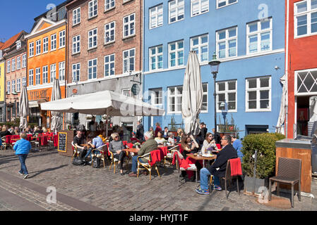 The historic waterfront restaurants in Nyhavn, Copenhagen, Denmark, attract many Copenhageners and tourists on a - Stock Photo