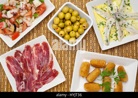 Food. Traditional tapas of the Andalusian gastronomy. Iberian ham with black leg, seafood salpicon, anchovies in - Stock Photo