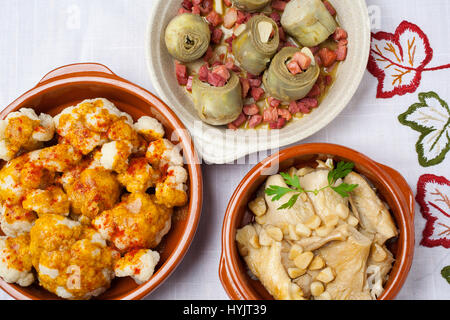 Food Tapas. Traditional gastronomic dishes of the Spanish gastronomy. Cauliflower with pimenton, artichokes with - Stock Photo