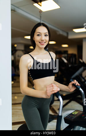 Young fit woman using an elliptic trainer in a fitness center and smiling. - Stock Photo