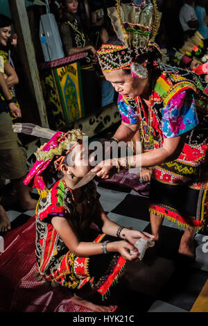 An old Dayaknese woman performs a blessing ritual to a young girl at the longhouse of Bali Gundi in Putussibau, - Stock Photo