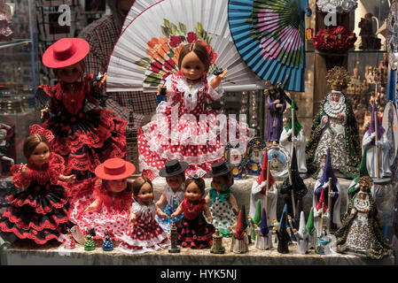Small child's flamenco dresses, fans and miniature dolls on sale at one of the many Spanish souvenir shops in Seville - Stock Photo