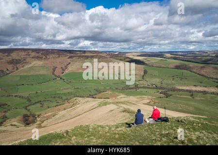 Two middle aged men enjoying the view from Lose Hill in the Peak District on a beautiful sunny spring day. - Stock Photo