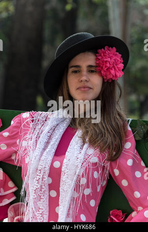A young girl tourist pose for a photo souvenir of herself as a flamenco dancer at a flamenco dress photo shoot stand - Stock Photo