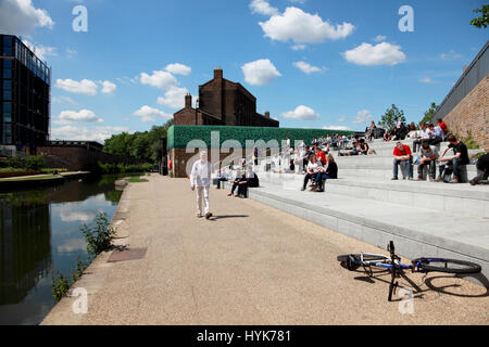 Students from Central St. Martins art school, UAL, enjoying the sun in Granary Square by Regent's Canal, King's - Stock Photo