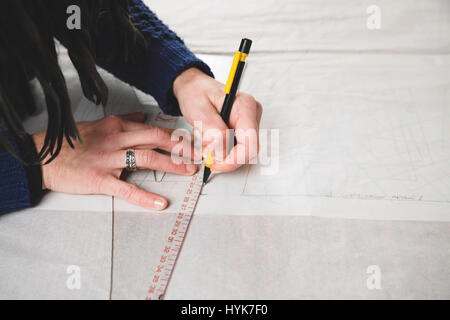 Hands of seamstress drawing templates in tracing paper using rules - Stock Photo