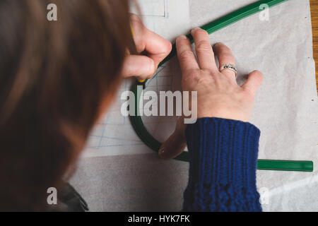 Hands of seamstress drawing templates in tracing paper using rules to make curves - Stock Photo