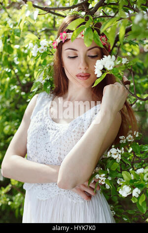 Beautiful woman in a flowered orchard. Spring seasonal - Stock Photo
