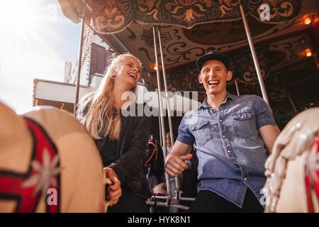 Smiling friends on amusement park carousel. Young couple on carousel ride. - Stock Photo