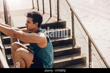 Fitness male doing stretching workout outdoors at the beach. Healthy young man stretching on a railing . - Stock Photo