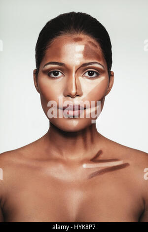 Close up portrait of young woman with contour and highlight makeup on face against white background. Female face - Stock Photo