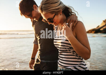 Portrait of happy young couple walking on sea shore. Man and woman on beach holiday. - Stock Photo