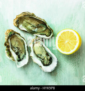 A square photo of freshly opened oysters with a slice of lemon, on a wooden background texture - Stock Photo