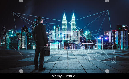 Rear view of a businessman looking at large city center with network connection graph . Concept of success and sociality. - Stock Photo