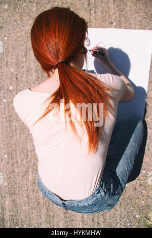 Young redhead woman drawing a poster - Stock Photo