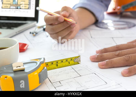 Interior designer discussing data and digital tablet and computer laptop with business document and graphics design - Stock Photo