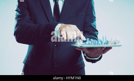 Success businessman using digital tablet show the city skyline on virtual screen , smart and modern city concept - Stock Photo
