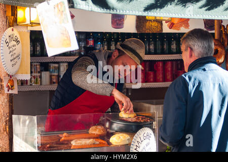 A tourist buys an hot dog at the traditional Christmas markets of Bolzano, in Italy. - Stock Photo