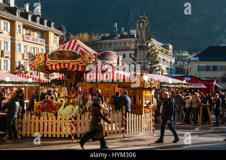 Cisitors attends next to a carousel at the traditional Christmas markets of Bolzano, in Italy. - Stock Photo