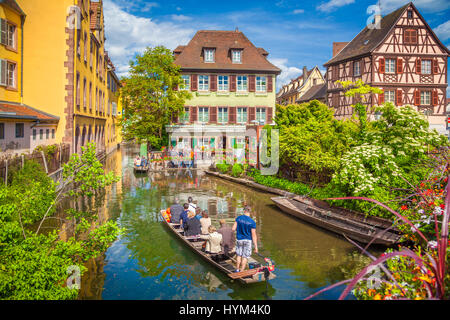 Beautiful view of the historic town of Colmar, also known as Little Venice, with tourists taking a boat ride on - Stock Photo