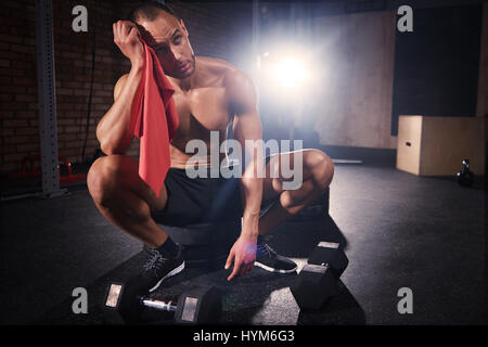 Young bodybuilder wiping sweat with towel - Stock Photo