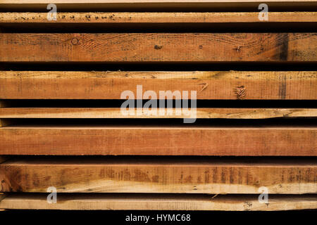 Wooden planks cut at sawmill and stacked in pile ready for use as building material - Stock Photo