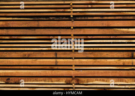 Different size sawn wooden planks stacked in pile and stored for use as building material - Stock Photo