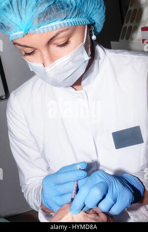 Microsurgery : Dermatologist performs local anesthesia on the hand - Stock Photo