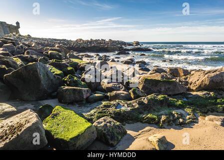 Rocks on the beach of Nevogilde civil parish in Porto, Portugal. Fort of Sao Francisco do Queijo (so called Castle - Stock Photo