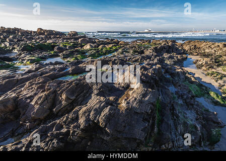 Rocky beach of Nevogilde civil parish of Porto, second largest city in Portugal. Cruise Terminal of Leixoes Port - Stock Photo