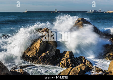Waves smashing against rocks on the beach in Nevogilde civil parish of Porto, Portugal. Port of Leixoes breakwater - Stock Photo