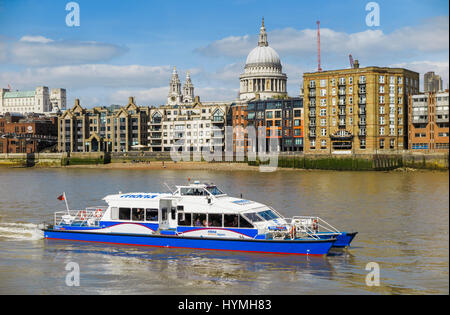 Blue and white Catamaran Thames Clipper boat forming part of the river bus service, Bankside pier, St Paul's in - Stock Photo