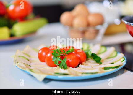 Food tray with delicious salami tomatoes, salad and vegetable - Stock Photo