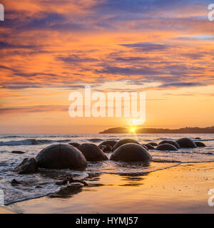 Sunrise at Moeraki Boulders, Otago, a major tourist attraction in the South Island of New Zealand. - Stock Photo