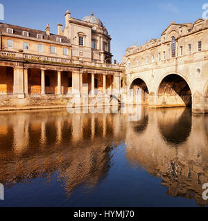 Pulteney Bridge and Colonnade, Bath, England, on a bright spring morning, reflected in the River Avon. The bridge - Stock Photo