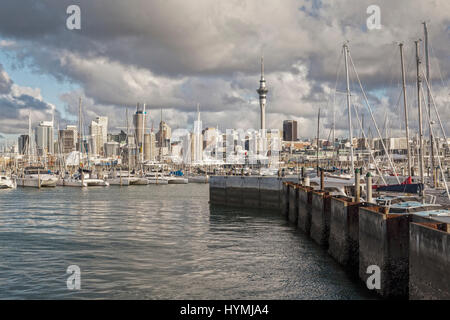 Auckland CBD and Westhaven Marina under a dramatic sunset sky. - Stock Photo