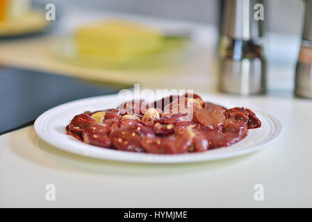 Raw Fresh chicken meat on white plate in kitchen - Stock Photo