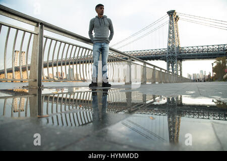 A young man waits along The East River, underneath the Williamsburg Bridge. Shot during an Autumn sunset in New - Stock Photo