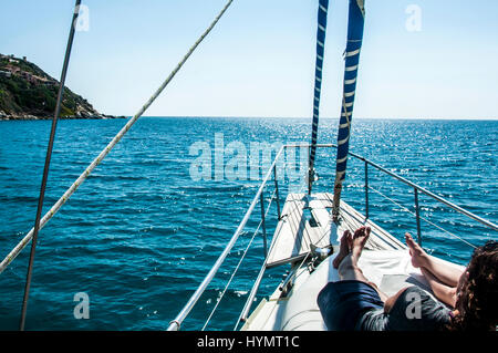 panoramic ocean and landscape shot of front of the yacht in summer time in italy sardinia with girl - Stock Photo