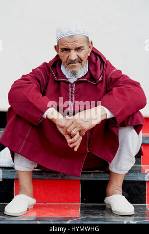 Elderly Muslim man, Ouarzazate, Morocco, 2016. A bearded Muslim man sitting on red and black tiled steps in the - Stock Photo