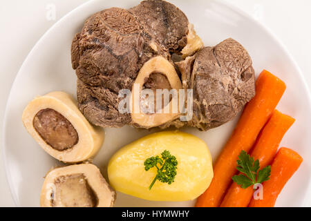 High angle view of a closeup of a pot au feu, a french beef stew on a white plate and background - Stock Photo